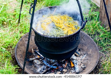 Outdoor hand dying of yarn in an iron pot boiling over open fire. Yarn and herbs present in the boiling water. - stock photo
