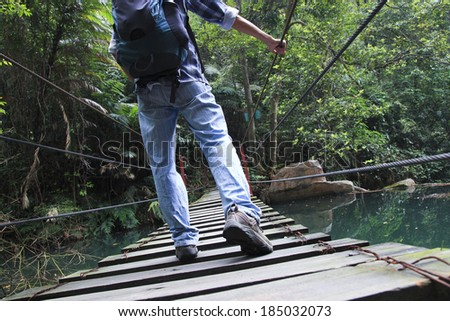 outdoor hanging bridge over the little winding brook in forest - stock photo