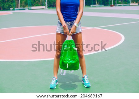 Outdoor image of woman with long tan sportive legs, wearing short vintage jeans shorts, holding her clear neon backpack and posing at american sports ground. - stock photo