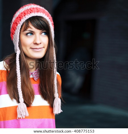 Outdoor lifestyle closeup portrait of young pretty young smiling woman posing in cold weather on the street in red hat  - stock photo