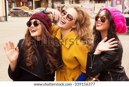 Outdoor lifestyle fashion portrait of three pretty cheerful girls friends, smiling and having  fun. Waving to someone. Walking on the autumn city. Wearing stylish bright outerwear, hats and sunglasses - stock photo