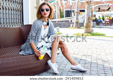 Outdoor lifestyle fashion portrait of woman posing on the street drinking orange smoothie, wearing stylish midi skirt, cardigan and sunglasses, joy, relax, vacation, travel. - stock photo