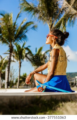 Outdoor lifestyle portrait of black young female in bright outfit and sunglasses. Hipster girl sitting at skate park with blue penny longboard skateboard. Sunny hot summer holiday day. Swag, fashion. - stock photo
