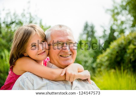 Outdoor lifestyle portrait of grandchild embracing grandfather - stock photo