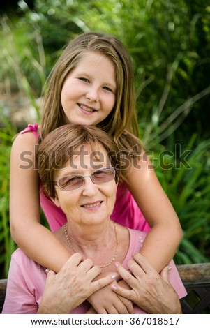 Outdoor lifestyle portrait of grandchild embracing grandmother - stock photo