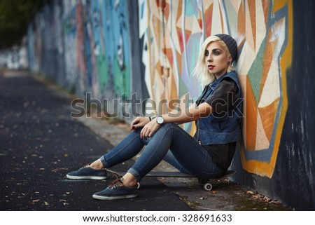 Outdoor lifestyle portrait of pretty young girl, wearing in hipster swag grunge style on urban background with graffiti. Retro vintage toned image, film simulation. - stock photo