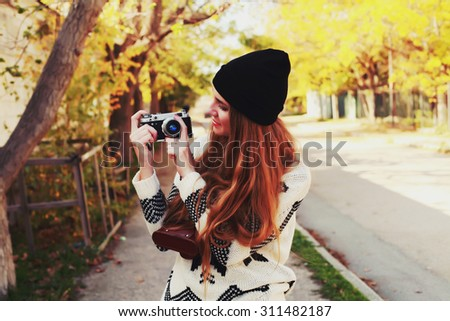 Outdoor lifestyle portrait of pretty young hipster woman making photo. Retro photographer. Modern urban girl has fun with vintage photo camera. Photo toned style Instagram filters. - stock photo