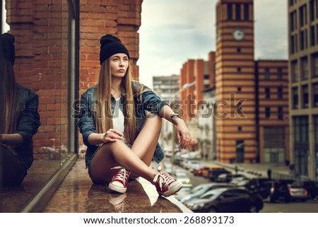 Outdoor lifestyle portrait of pretty young sitting girl, wearing in hipster swag grunge style urban background. Retro vintage toned image, film simulation. - stock photo