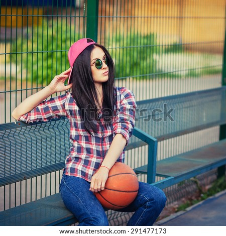 Outdoor lifestyle portrait of pretty young sitting girl, wearing in hipster swag grunge style with basketball in urban background. Retro vintage toned image, film simulation. - stock photo