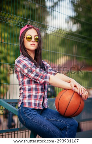 Outdoor lifestyle portrait of pretty young sitting girl, wearing in hipster swag grunge style with basketball urban background. Retro vintage toned image, film simulation. - stock photo