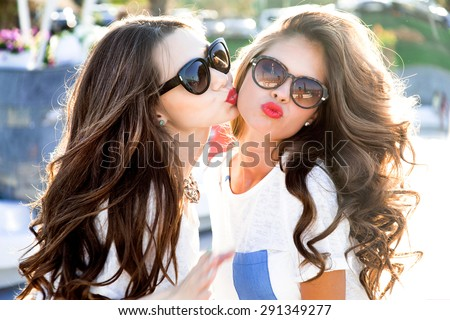 Outdoor lifestyle portrait of two best friends hipster girls wearing stylish bright outfits,  denim shorts and glasses, going crazy and having great time together.Laughing and send kiss,lovely friends - stock photo