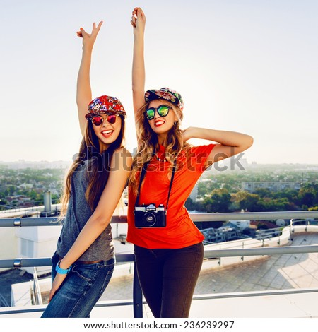 Outdoor lifestyle portrait of two crazy happy best friend girls screaming and put their hands to the air, enjoy amazing view from the roof at sunset, wearing trendy bright clothes caps and sunglasses. - stock photo