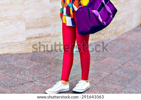 Outdoor lifestyle portrait of young stylish hipster girl, walking on the street, wearing bright clothes and big sportive bag, cropped photo. - stock photo