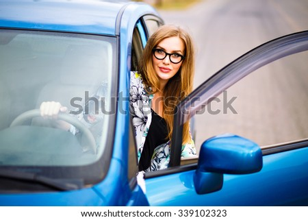 Outdoor lifestyle portrait of young traveler hipster girl driving car, making stop and relax, nice day, travel joy concept. - stock photo