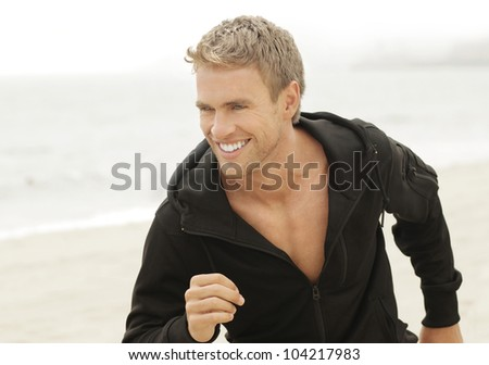 Outdoor natural portrait of a good looking young blond man running along beach with smile - stock photo