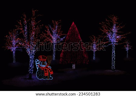 Outdoor night shot of Illuminated trees and Snowman for the perfect Christmas atmosphere - stock photo