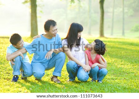 Outdoor park happy Asian family - stock photo