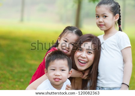 Outdoor park happy Asian mother and children - stock photo