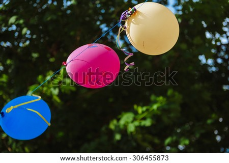 outdoor party in garden decorated with colorful balloons. Vivid color balloons on green outdoor background - stock photo