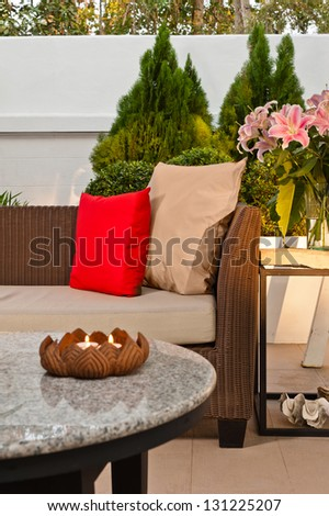 Outdoor patio seating are with nice Rattan sofa at sunset - stock photo