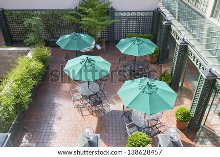 Outdoor Patio Seatings with Tables Chairs and Green Umbrellas - stock photo