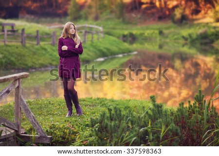 Outdoor photo from a beautiful young women standing before small lake in a park, with a violet colored clothing at autumn - stock photo