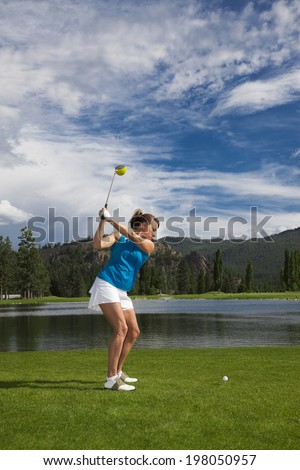Outdoor photo of attractive woman golfing. - stock photo