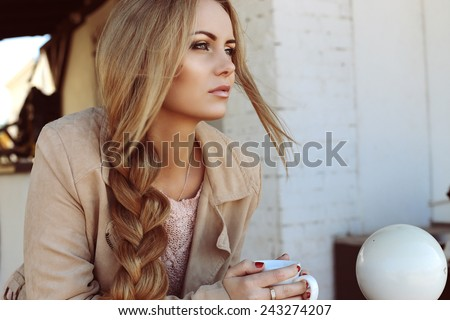 Outdoor photo of beautiful blond woman with long hair and perfect makeup wearing knitted sweater and scarf and posing at autumn park - stock photo