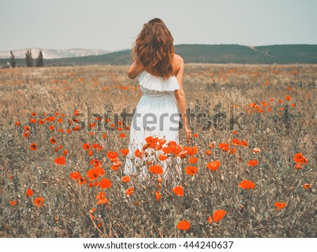 Outdoor photo of beautiful young woman in the poppy field - stock photo