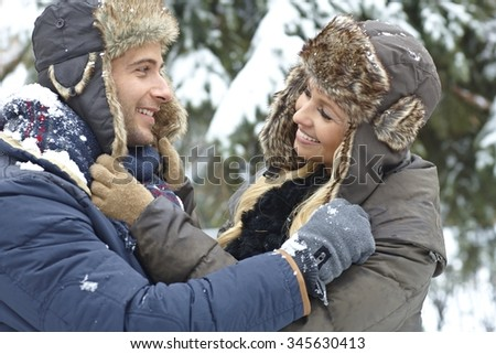 Outdoor photo of loving couple embracing at wintertime, smiling happy. - stock photo