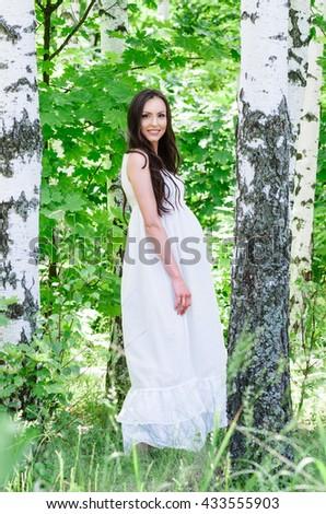 Outdoor photo of pregnant woman near the birch. - stock photo