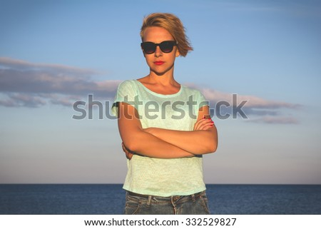 Outdoor photo of sexy beautiful elegant woman with short blonde hair resting on the summer beach next to the blue sea - stock photo