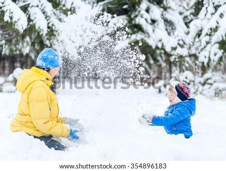 Outdoor portrait Mother and child playing in the winter park. showered with snow - stock photo