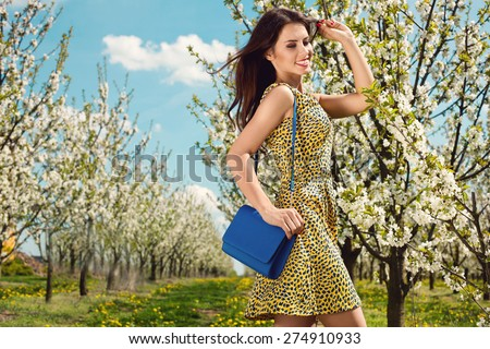 outdoor portrait of a beautiful brunette woman in yellow dress, blue handbag among blossom cherry trees - stock photo