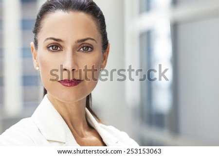 Outdoor portrait of a beautiful smart middle aged brunette woman or businesswoman - stock photo