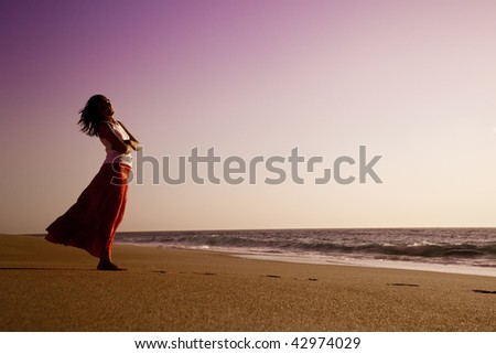 Outdoor portrait of a beautiful woman relaxing on the beach - stock photo