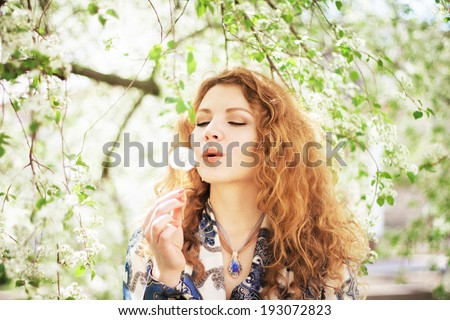 Outdoor portrait of a beautiful woman with dandelion  - stock photo