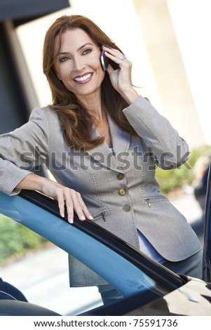 Outdoor portrait of a beautiful young brunette woman or businesswoman leaning on her car and talking on a cell phone - stock photo