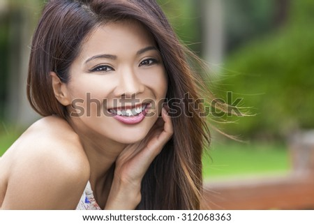 Outdoor portrait of a beautiful young Chinese Asian young woman or girl with perfect teeth, smiling and resting in her hand - stock photo