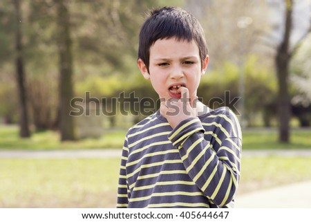 Outdoor portrait of a child boy with a finger in his mouth touching a loose tooth.  - stock photo