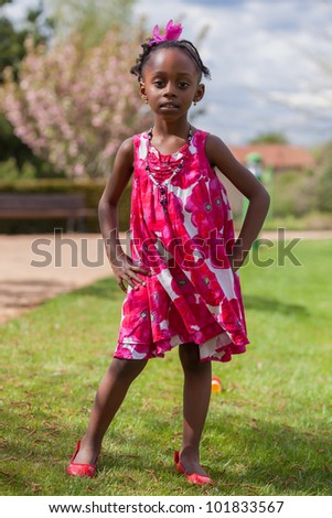 Outdoor portrait of a cute african american little girl, with the hands on the hips - stock photo