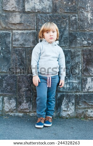 Outdoor portrait of a cute little boy against stone wall - stock photo