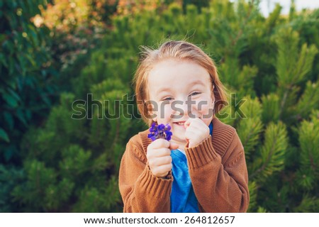 Outdoor portrait of a cute little boy of 4 years old, holding first spring flowers violets - stock photo