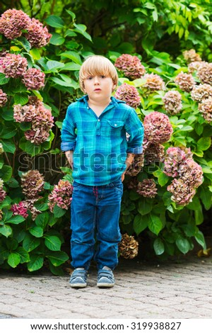Outdoor portrait of a cute little boy of 4 years old, wearing emerald shirt and denim jeans - stock photo