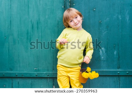 Outdoor portrait of a cute little boy, wearing yellow pullover and trousers, standing by the green wooden door, holding bucket with flowers dandelions. - stock photo