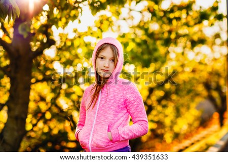 Outdoor portrait of a cute little girl of 8-9 years old at sunset, wearing bright pink hoody - stock photo