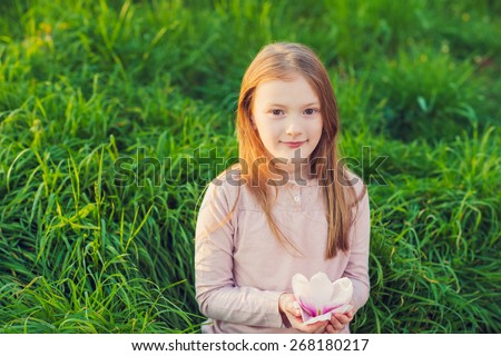 Outdoor portrait of a cute little girl on sunset, playing in the park with big magnolia flower - stock photo