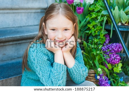 Outdoor portrait of a cute little girl sitting on steps in a city on a nice spring day - stock photo