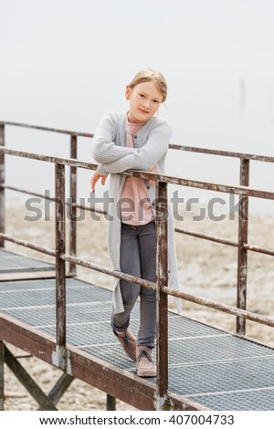 Outdoor portrait of a cute little girl, wearing grey trousers and long cardigan, standing on small bridge - stock photo