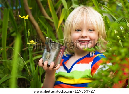 Outdoor portrait of a cute smiling child drinking milk in the garden looking at camera - stock photo
